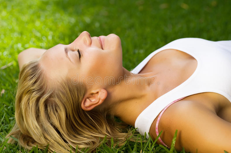 Beautiful Girl lying on the grass. Beautiful Young Woman lying on the grass.Close-up image stock photos