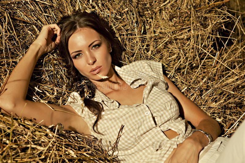 Beautiful girl lying in a haystack royalty free stock photo