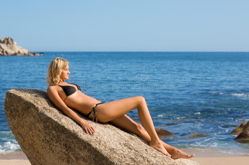 Beautiful girl lying on a rock. By the sea royalty free stock photo