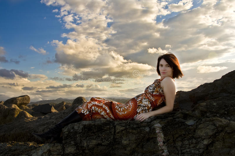 Beautiful girl lying on rocks. At the beach stock images