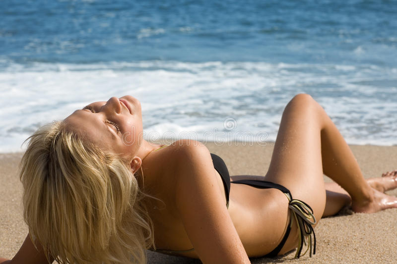 Beautiful girl lying on the sand by the sea. Sunny day royalty free stock photography