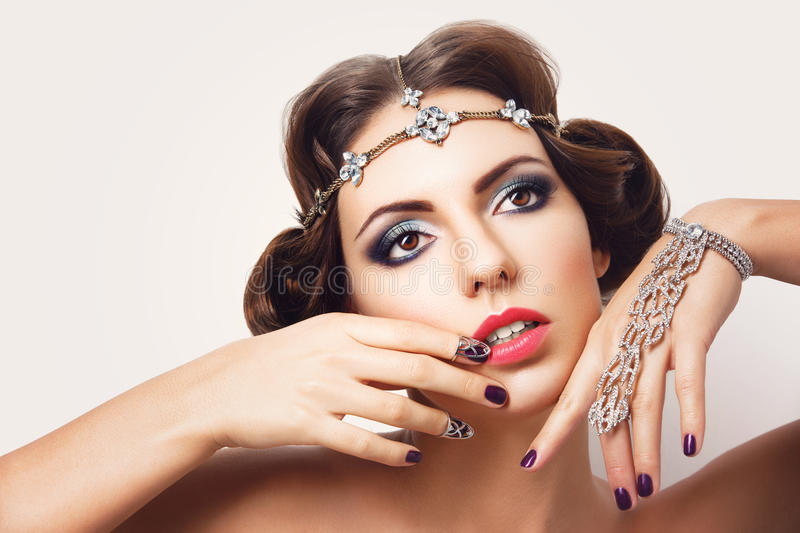 Beautiful girl with make-up and jewelry. Gorgeous retro style young woman with bright makeup and fancy hairdo. Hair and hand jewelry accessories. Over white royalty free stock image