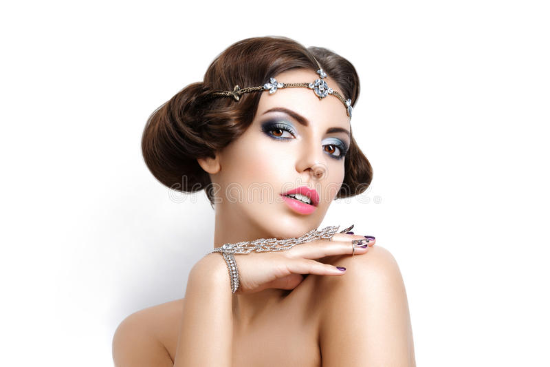 Beautiful girl with make-up and jewelry. Gorgeous retro style young woman with bright makeup and fancy hairdo. Hair and hand jewelry accessories. Over white royalty free stock photo