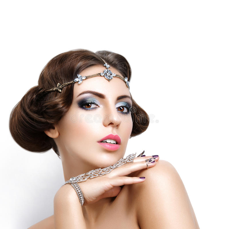 Beautiful girl with make-up and jewelry. Gorgeous retro style young woman with bright makeup and fancy hairdo. Hair and hand jewelry accessories. Over white royalty free stock photos