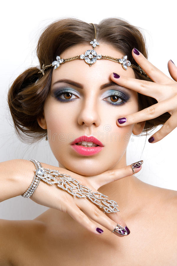 Beautiful girl with make-up and jewelry. Gorgeous retro style young woman with bright makeup and fancy hairdo. Hair and hand jewelry accessories. Over white royalty free stock photography