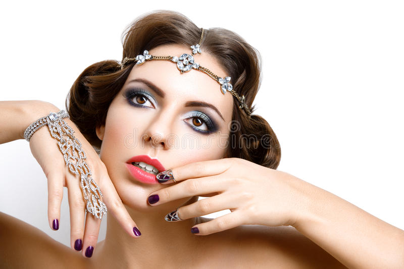 Beautiful girl with make-up and jewelry. Gorgeous retro style young woman with bright makeup and fancy hairdo. Hair and hand jewelry accessories. Over white stock image