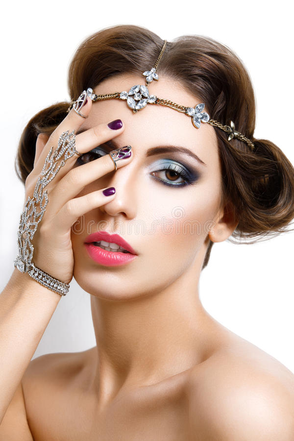 Beautiful girl with make-up and jewelry. Gorgeous retro style young woman with bright makeup and fancy hairdo. Hair and hand jewelry accessories. Over white stock photography