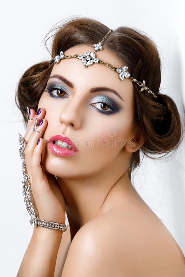 Beautiful girl with make-up and jewelry. Gorgeous retro style young woman with bright makeup and fancy hairdo. Hair and hand jewelry accessories. Over white stock photos