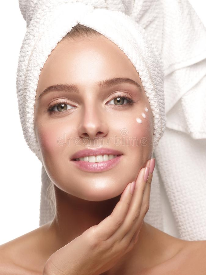 Beautiful girl without make up and with the white towel on her head does daily skincare royalty free stock image