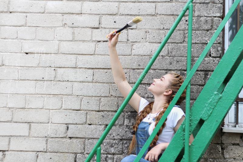 The girl makes preparing for painting a wooden surface gazebo, fence royalty free stock images