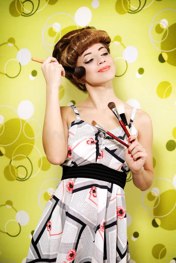 Beautiful girl with makeup brushes stock images