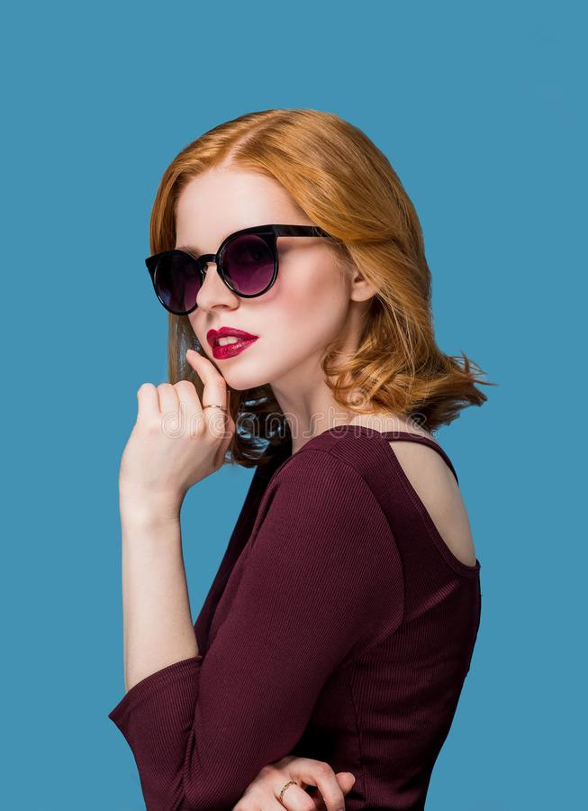 Beautiful girl with makeup and red lips in the Burgundy jacket in sunglasses stock image