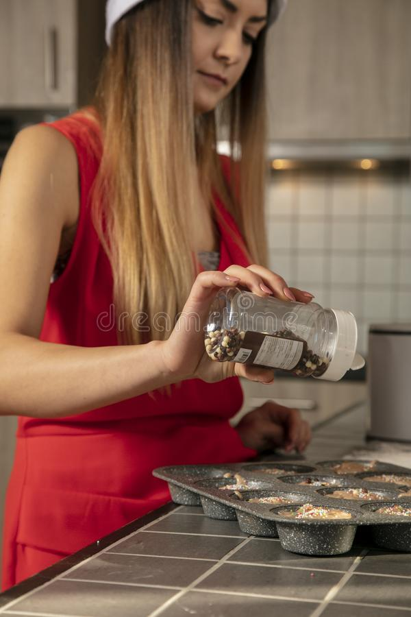 Beautiful girl is making cupcakes for the holidays stock images