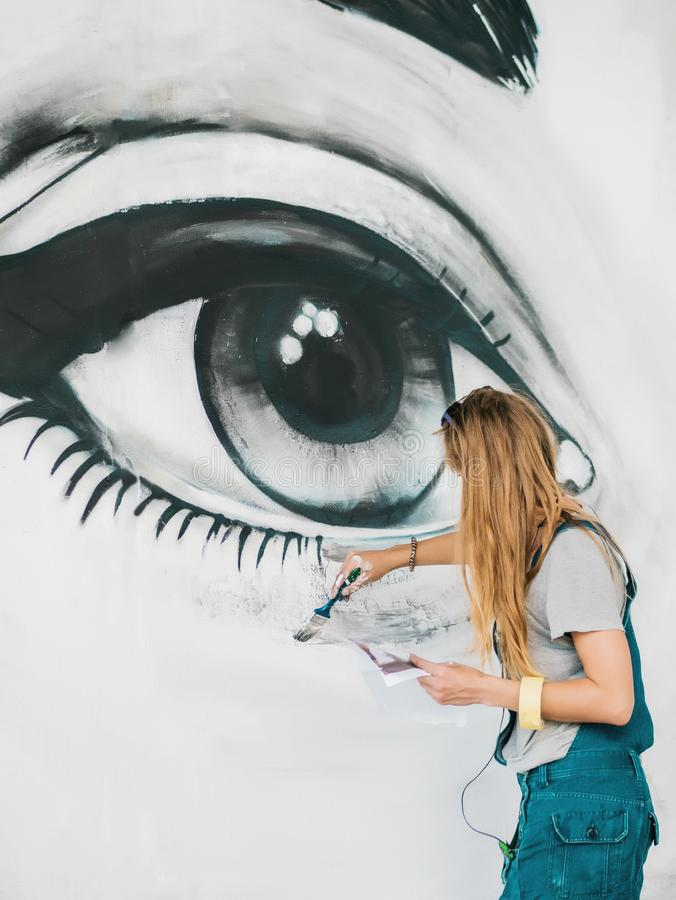 Beautiful girl making graffiti of big female face with aerosol spray on urban street wall. Creative art. Talented stock photos