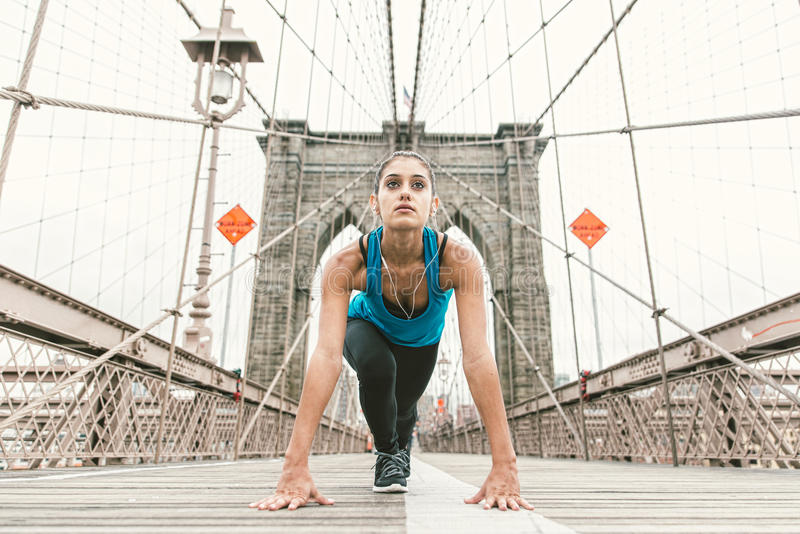 Beautiful girl making stretching at early morning before running. brooklyn bridge and new york skyline in the background stock images
