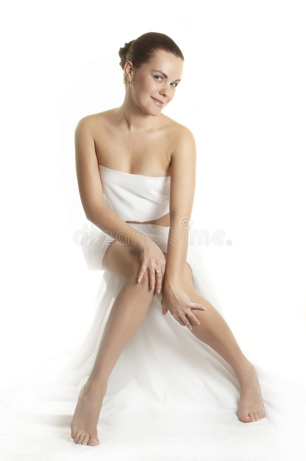 Beautiful girl before massage. The girl in a white fabric smiles stock photography