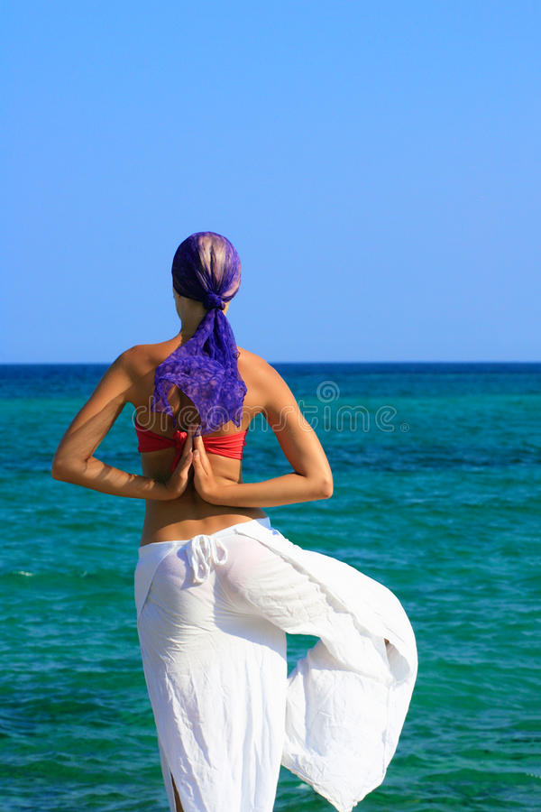 Beautiful girl meditating on the beach stock image