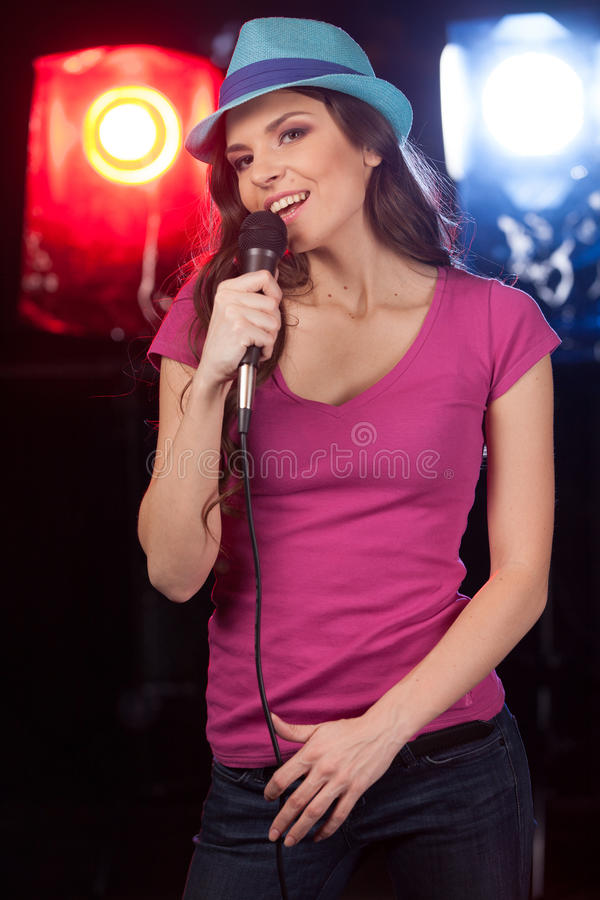 Beautiful girl with microphone standing in bar. stock photos