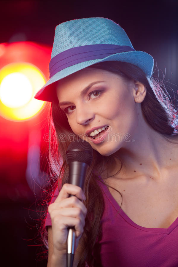 Beautiful girl with microphone standing in bar. stock photo