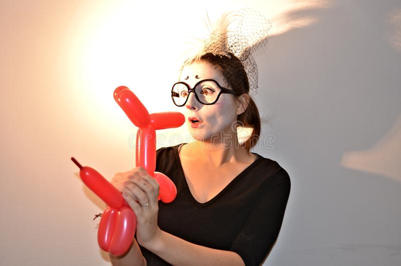 Beautiful girl-mime holding balloon dog. royalty free stock images