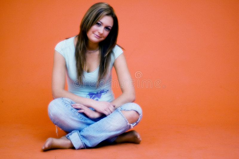 Beautiful Girl (Minor). With long dark hair, sitting crosslegged on floor, wearing jeans with hole in knee and low cut t-shirt, orange background stock images