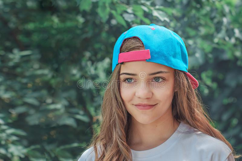 Beautiful girl model in a baseball cap with flowing hair on the background of green shrubs or trees. Portrait of a happy stock photo