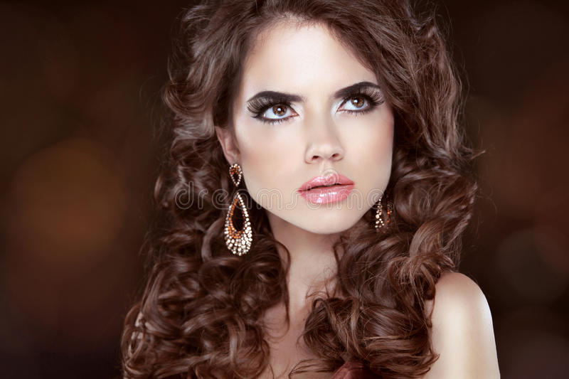 Beautiful girl model with curly long hair and fashion earrings stock photography