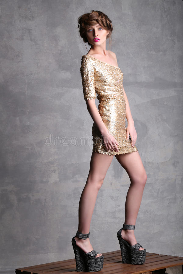 Beautiful girl model in gold dress at full height stock photo