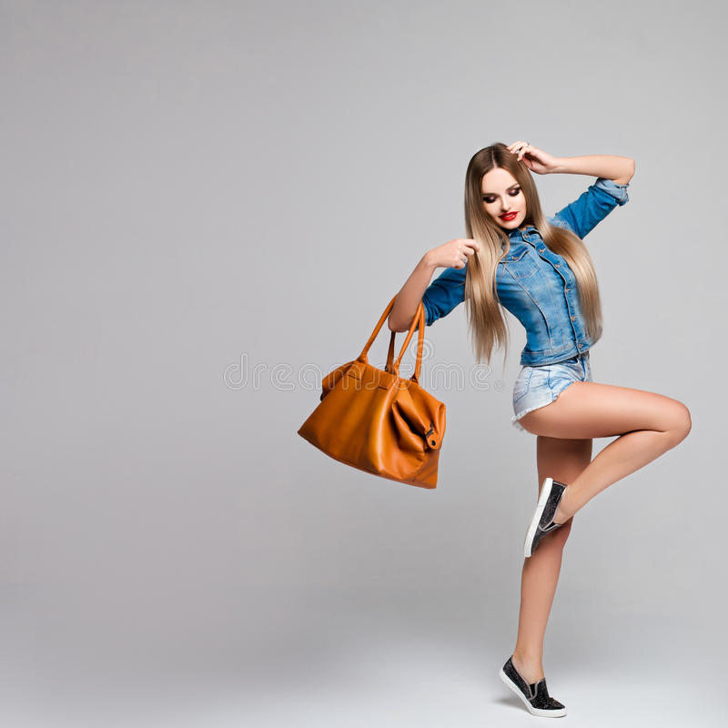 Beautiful girl in motion in a denim outfit with a large orange bag in her hand. Fashionable woman with long hair and stock images