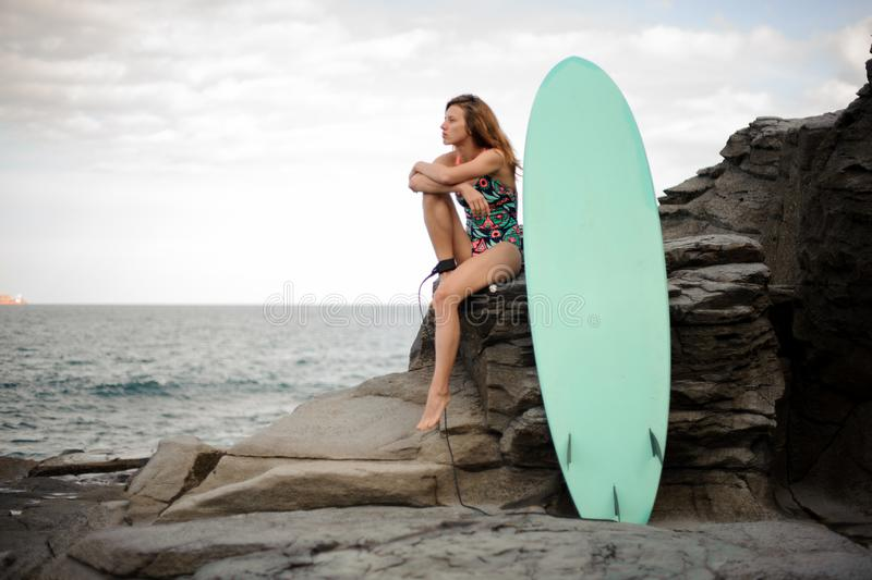 Beautiful girl in the multi colored swimsuit sitting near the surf on the rock stock photography