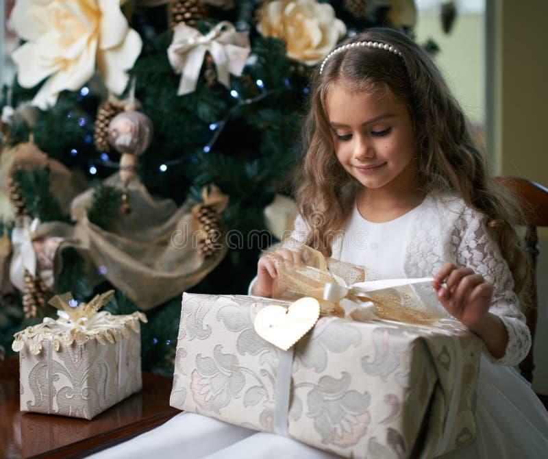 Beautiful girl near Christmas tree unpacking presents stock photo