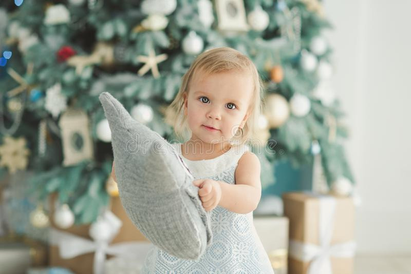 Beautiful girl near decorated Christmas tree with toy wooden rocking horse. Happy new year. Portrait little girl royalty free stock image