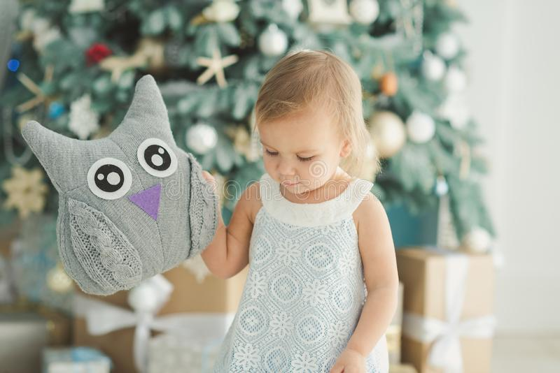 Beautiful girl near decorated Christmas tree with toy wooden rocking horse. Happy new year. Portrait little girl royalty free stock photography