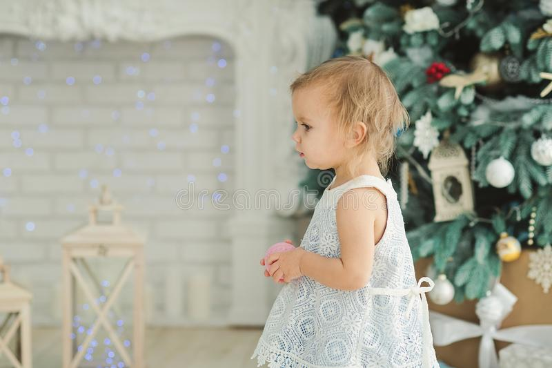 Beautiful girl near decorated Christmas tree with toy wooden rocking horse. Happy new year. Portrait little girl stock photos