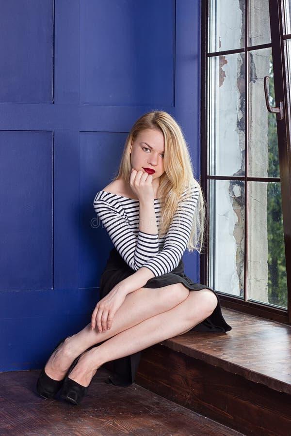 Beautiful girl near the windows at home stock image
