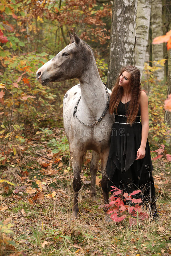 Beautiful girl with nice dress standing next to nice horse royalty free stock photos