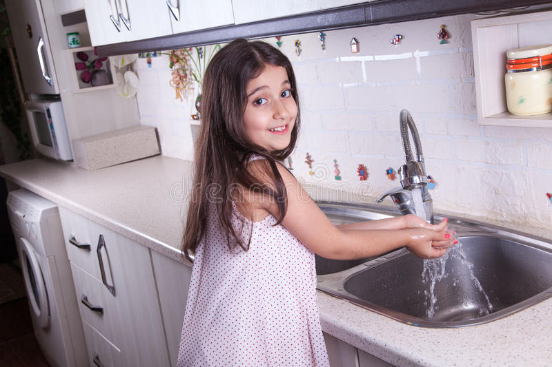 Beautiful girl in the nice white kitchen (series). One beautiful middle eastern little girl with pink dress and long dark brown hair and eyes on white kitchen royalty free stock photos