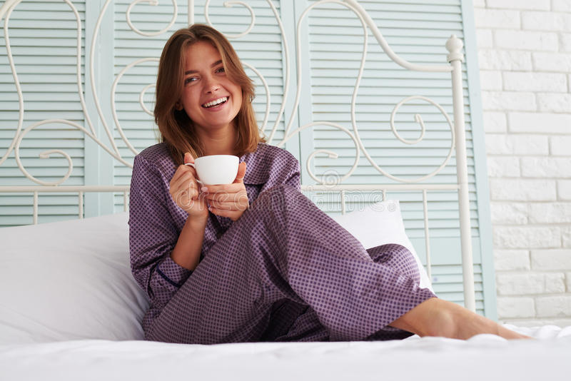 Beautiful girl in night-suit sitting at the bedside with a cup o royalty free stock photo