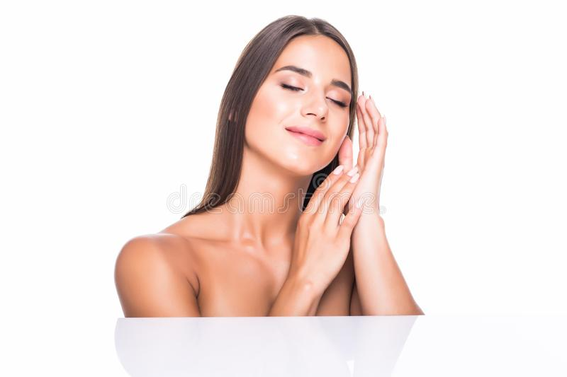 Beautiful girl with nude make up posing at grey studio background. Beauty photo concept, looking at camera, perfect skin. stock photo