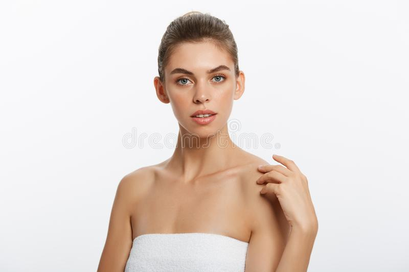 Beautiful girl with nude make up posing at white studio background, beauty photo concept, looking at camera, perfect stock photography