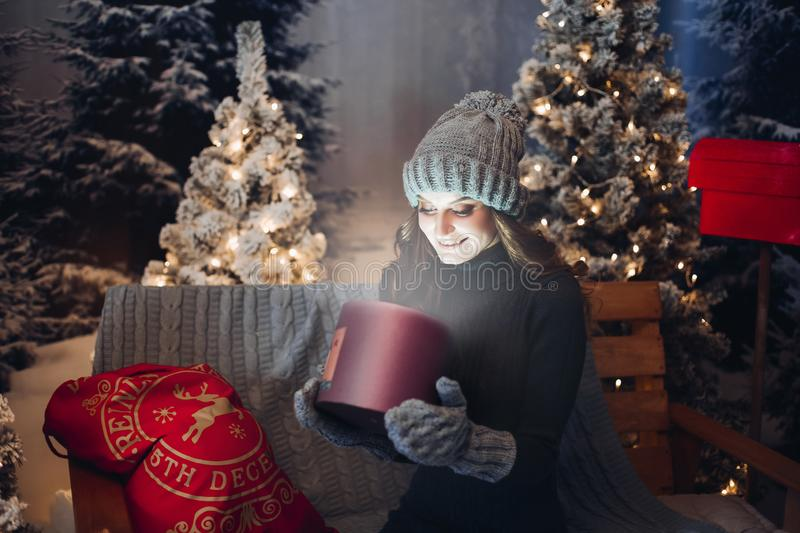 Beautiful girl opening magic box with present at Christmas night. royalty free stock image