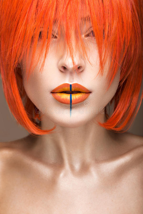 Beautiful girl in an orange wig cosplay style with bright creative lips. Art beauty image. Portrait shot in the studio stock photos
