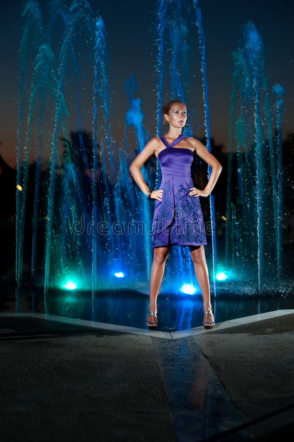 Beautiful girl at outdoor water fountain in a night stock image