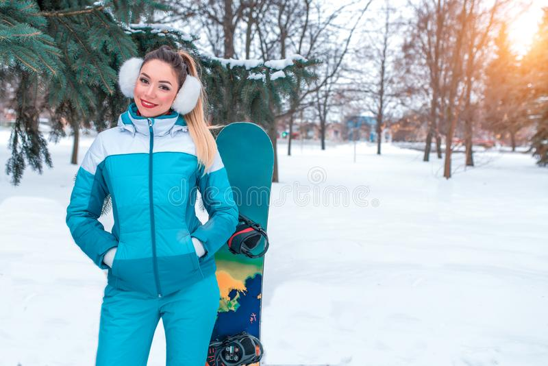 Beautiful girl in overalls on a background of snow, snowboard board. Emotions of happiness of pleasure of the woman on royalty free stock photos