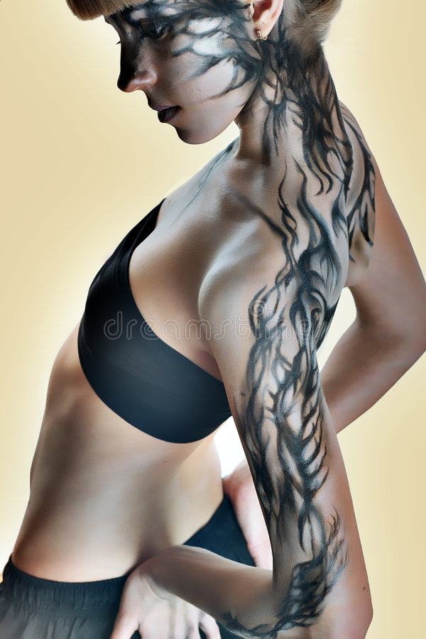 Beautiful girl with a paint on her skin. Blond stock photo