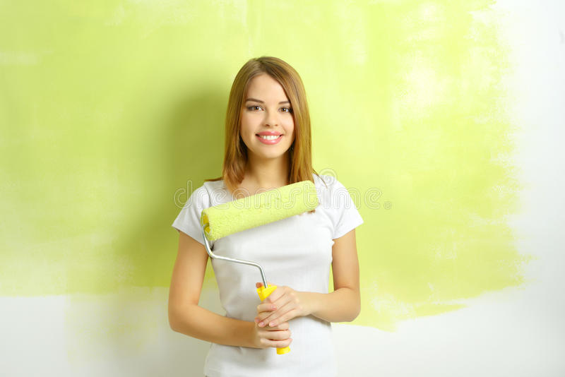 Beautiful girl painting a wall stock photography
