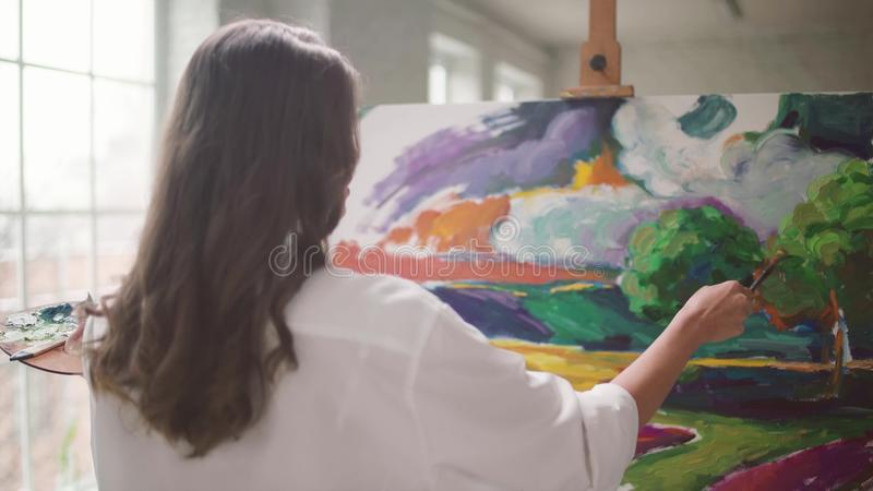 Beautiful girl paints on canvas stock footage