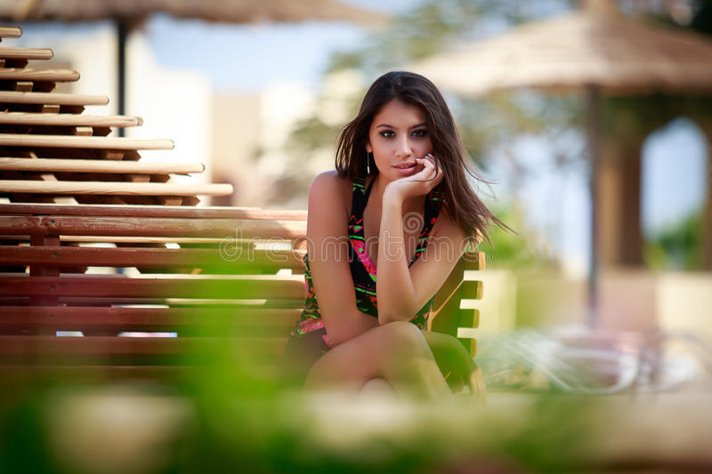 Beautiful girl in park, fashion model portrait outdoors. Beautiful girl with long brown hair in the park sitting on the bench, fashion model portrait outdoors royalty free stock photos