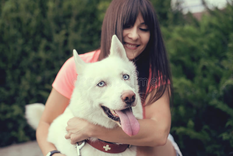 Beautiful girl in the park playing with her Husky dog royalty free stock photo