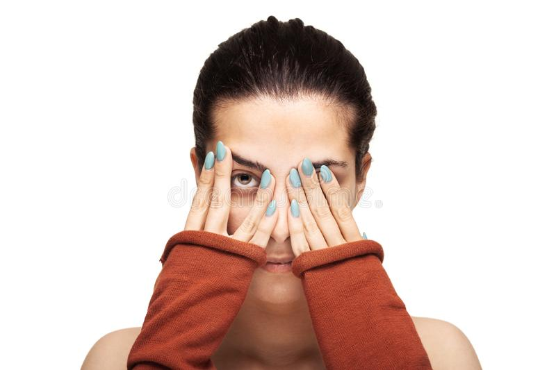 Beautiful girl peaking while hiding her face stock photography